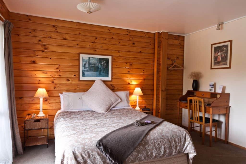 Przytulna sypialnia z drewnianą boazerią na ścianie i łóżkiem z szarą pościelą
