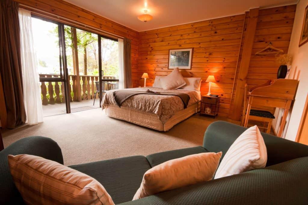 Sypialnia w stylu lodge z drewnianymi ścianami, wykładziną dywanową i przytulnym łóżkiem