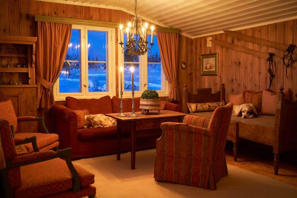 Przytulna górska sypialnia z drewnianą boazerią, brązowymi meblami i świeczką zapaloną żyrandolem