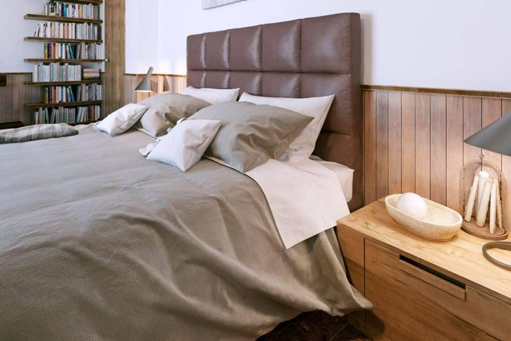 Przytulny drewniany rustykalny salon z szarą pościelą i drewnianymi panelami
