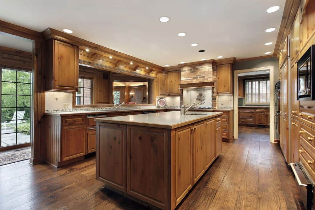 A craftsman inspired kitchen area with wooden cabinetry, wooden flooring, and granite countertops