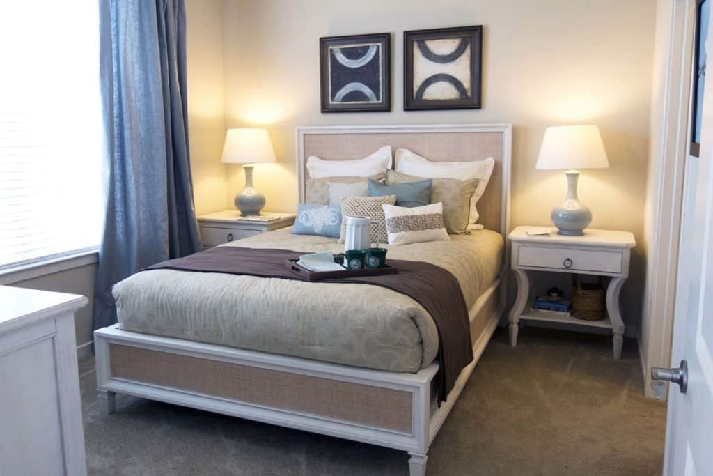 A cream painted bedroom with a classic designed bed, two nightstands with lampshades, and a gray carpeted flooring