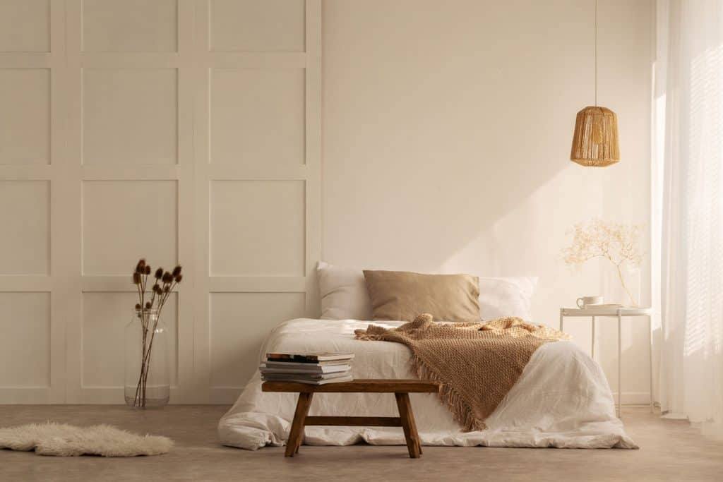 A cream painted bedroom with a white and brown beddings with a small wooden stool with books on it