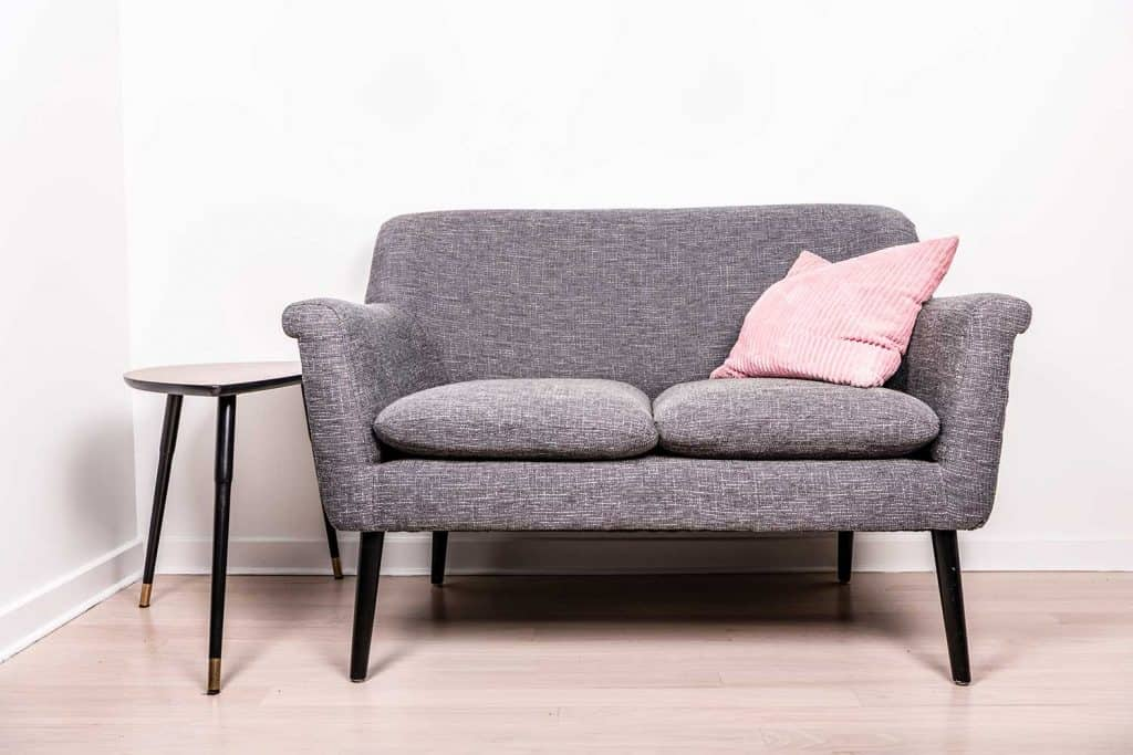 A cute gray settee with a pink pillow next to a small contemporary occasional table