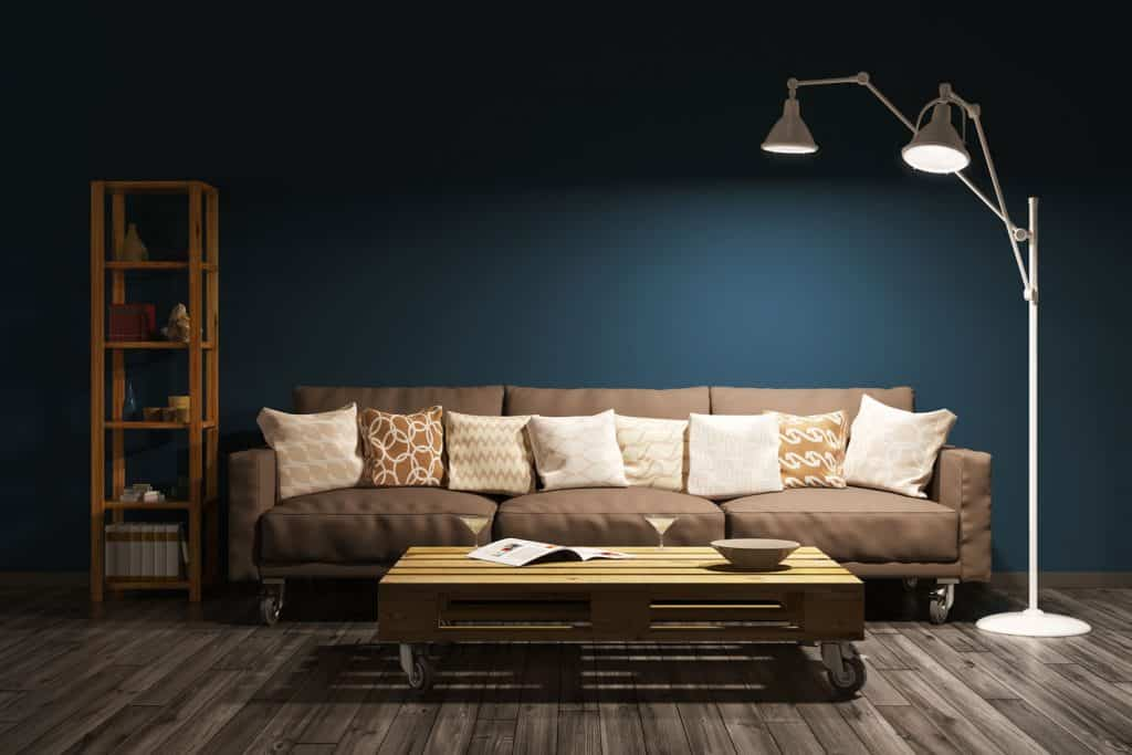 A dark blue wall living room with wooden flooring, brown sofa, and a coffee table in front