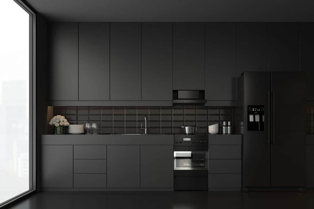 A dark themed kitchen counter with black paneled hanging cabinets and black paneled lower cabinets