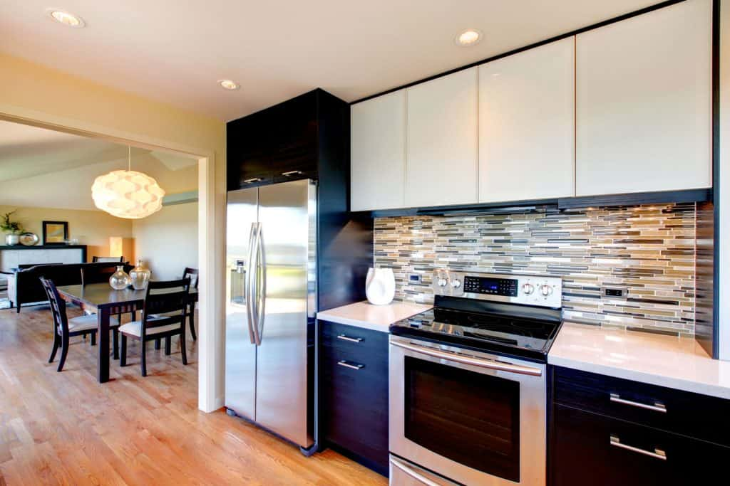 A farmhouse themed kitchen with decorative brick styled kitchen wall and a black colored cabinet panel