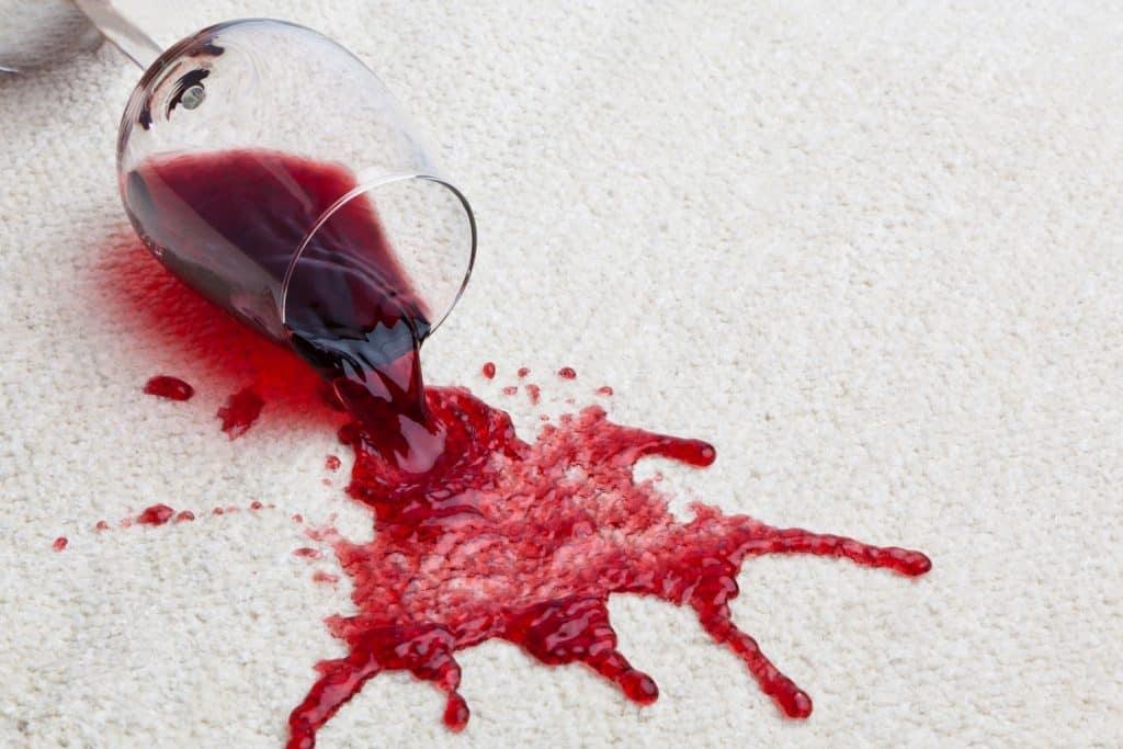 A glass of wine spilled on a carpet