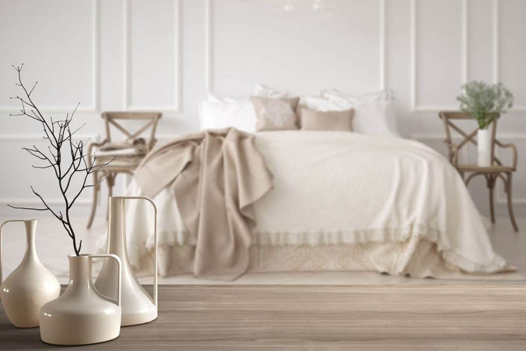 A gorgeous bedroom with cream painted walls, cream beddings and vases placed on top of a table