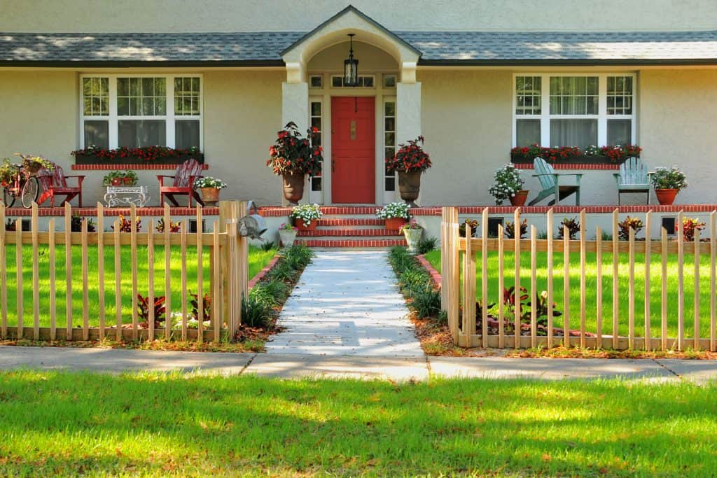 A gorgeous front entryway of a house with wooden fences, wooden paneled walls, and a red door