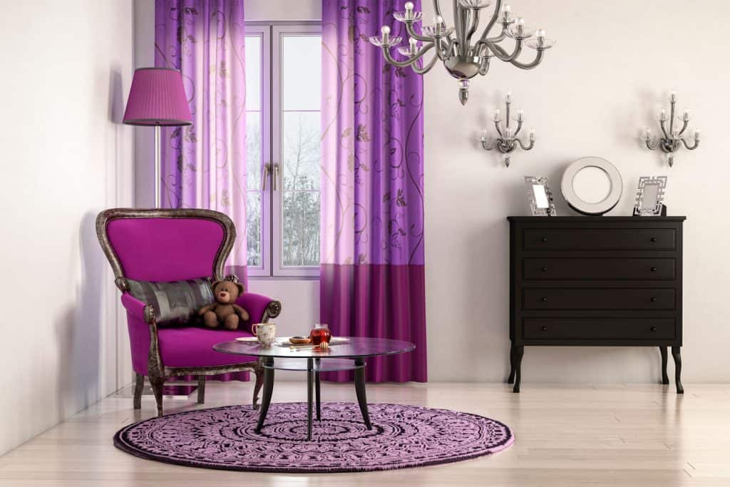 A gorgeous living room with a violet chair, curtains, and circular carpet with a small glass table on it
