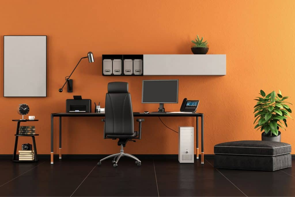 A gorgeous living room with an orange wall with an office desk placed close to the wall