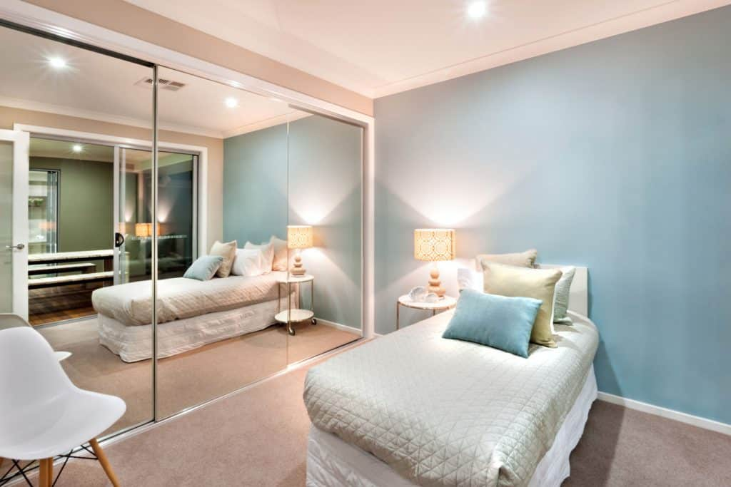 A gorgeous modern house with a single bed with teal colored pillows inside a blue painted bedroom