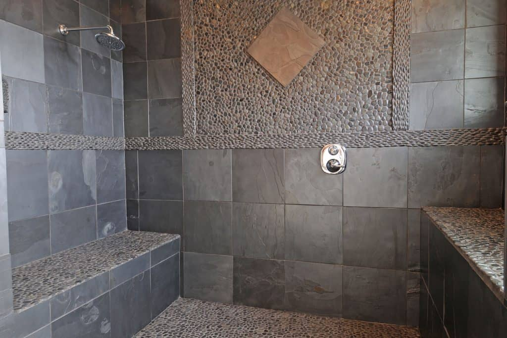 A gray tiled bathroom with decorative wash out pebbles