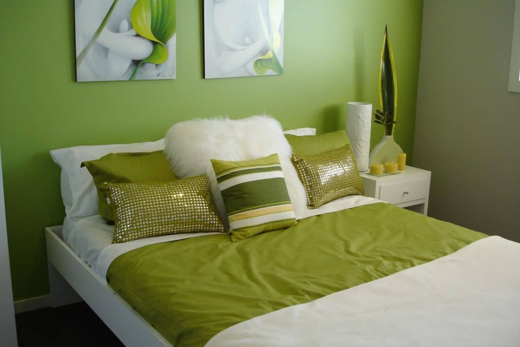 A green color inspired bedroom with a green wall, bed with green pillows and green sheets