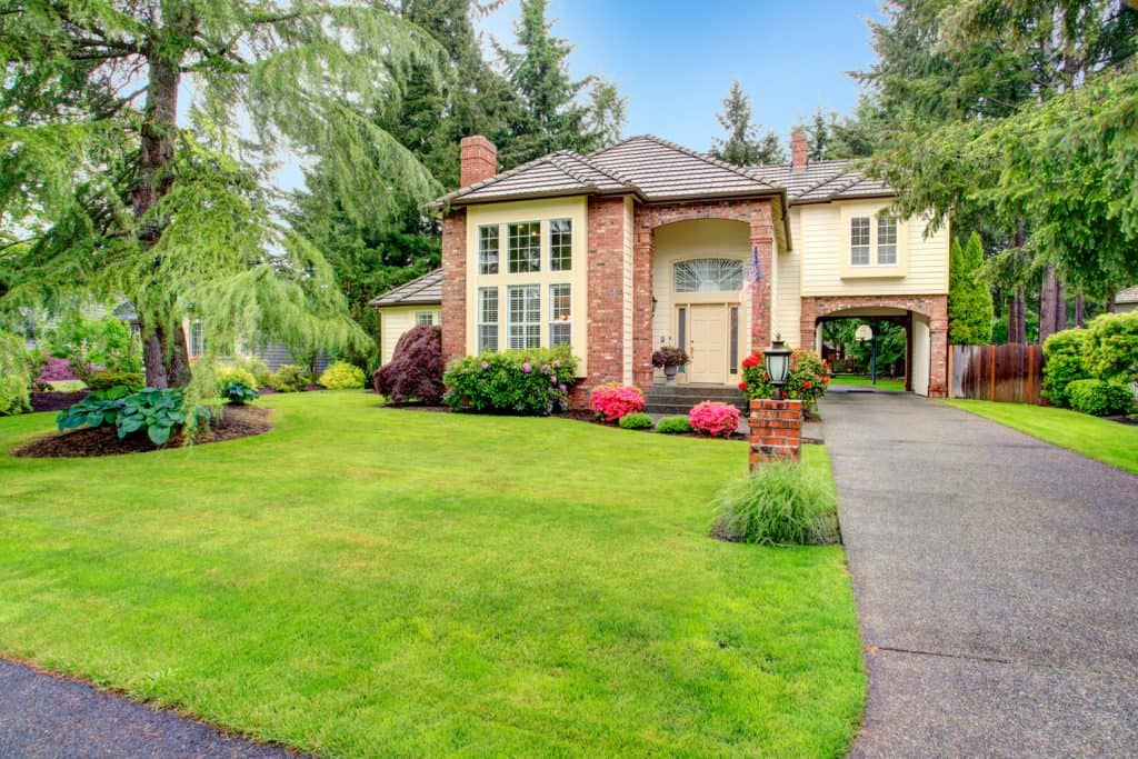 A huge mansion with asphalt shingles, yellow painted sidings, and a gorgeous landscape on the front yard
