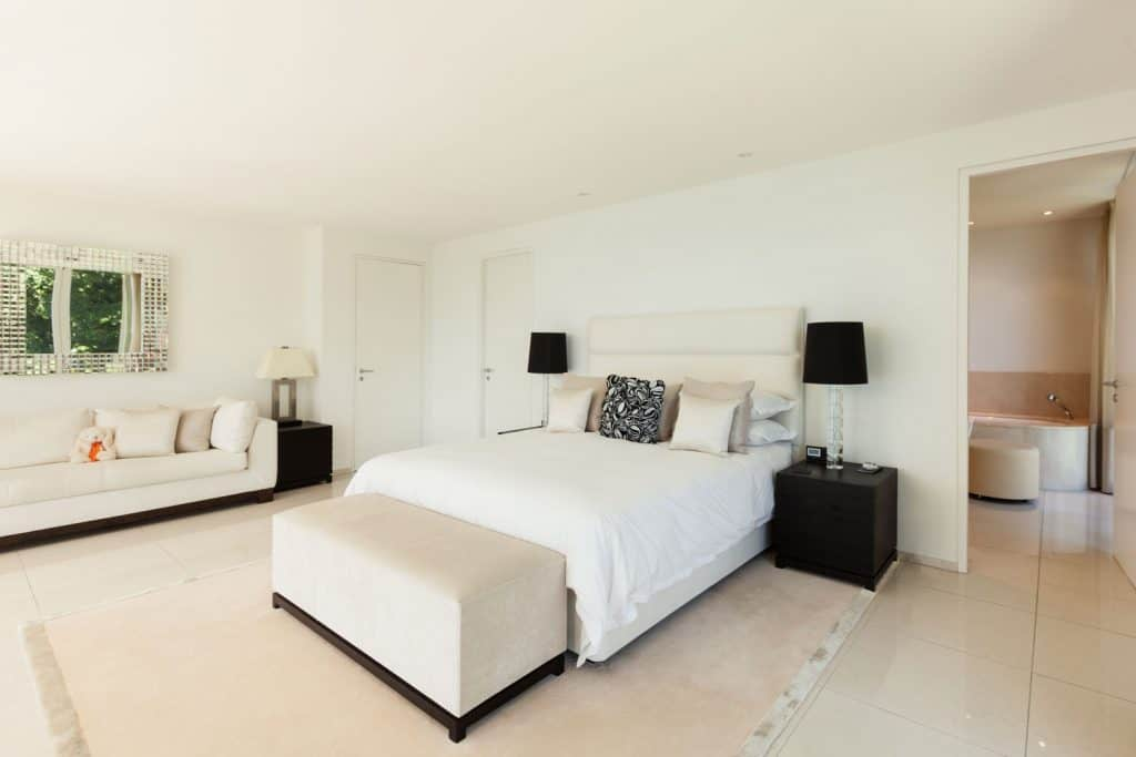 A huge white themed bedroom with a white bed mixed with dark nightstands and lampshade