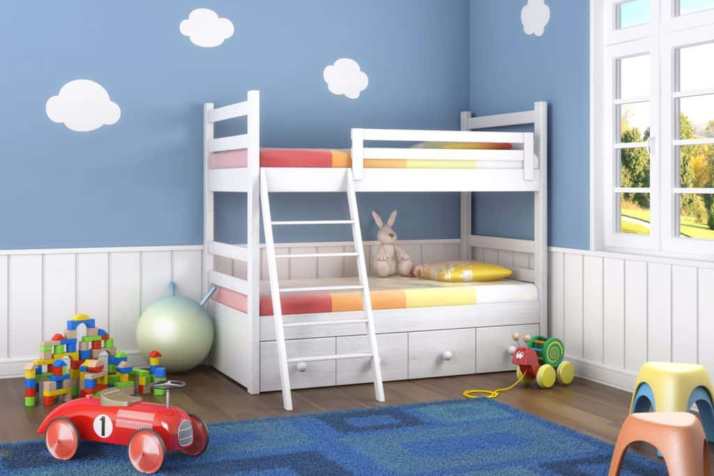 Kids room with blue walls decorated with clouds and a blue carpet on the middle of the room
