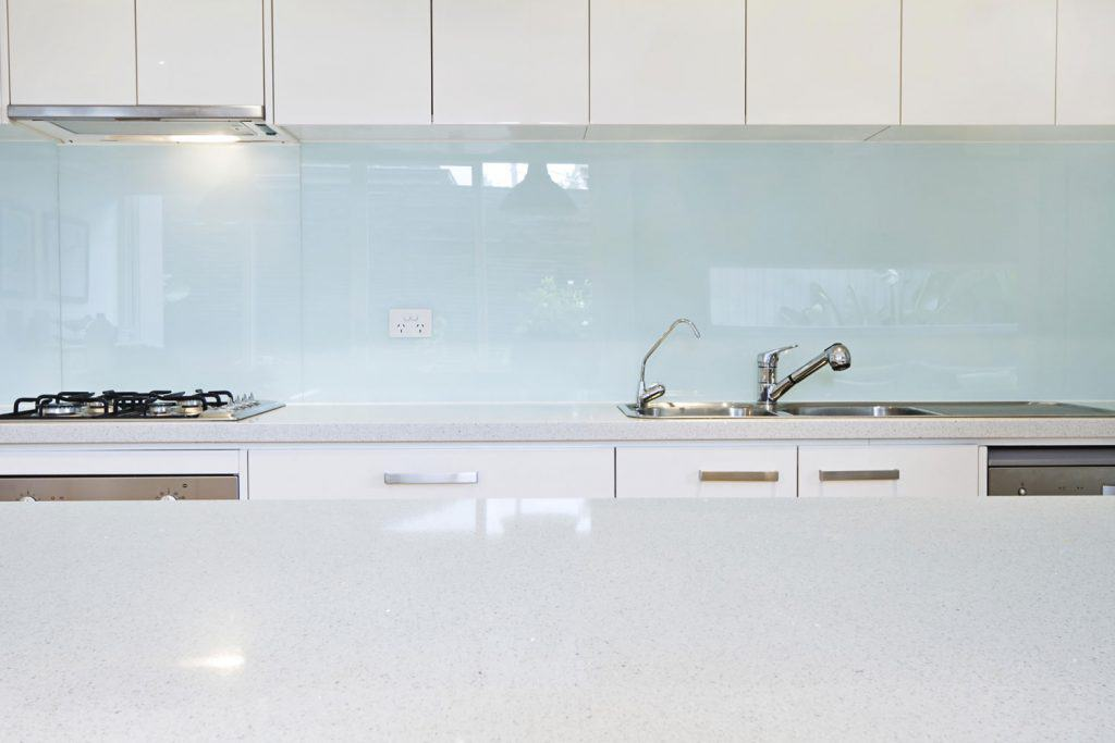 A light blue backsplash on the kitchen wall with white paneled cabinets