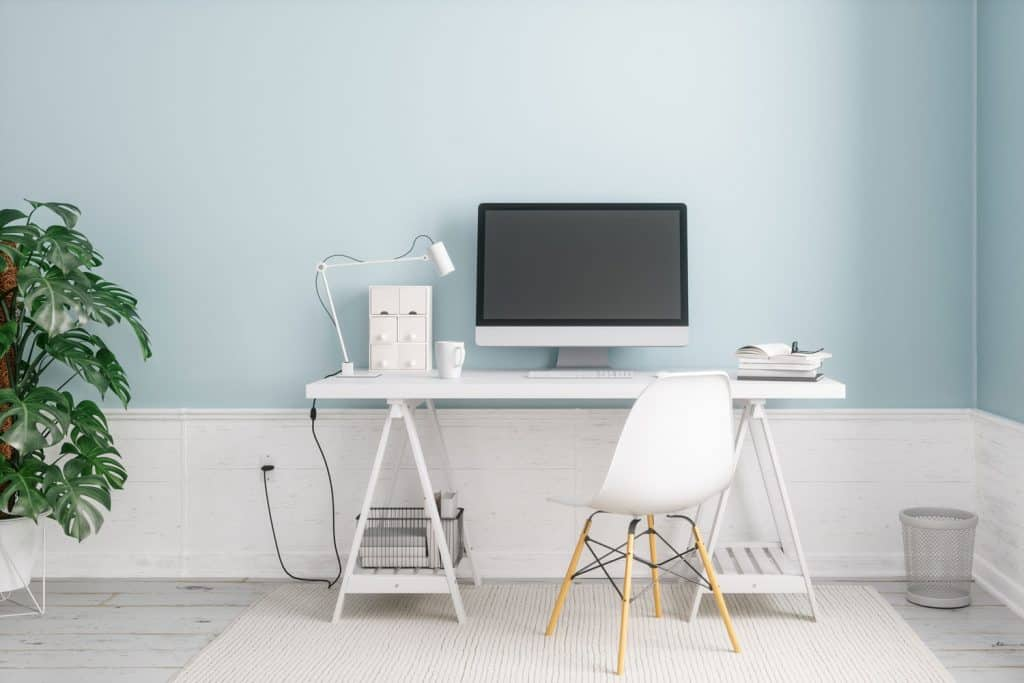A light blue colored living room with a white baseboard and a computer on the working table