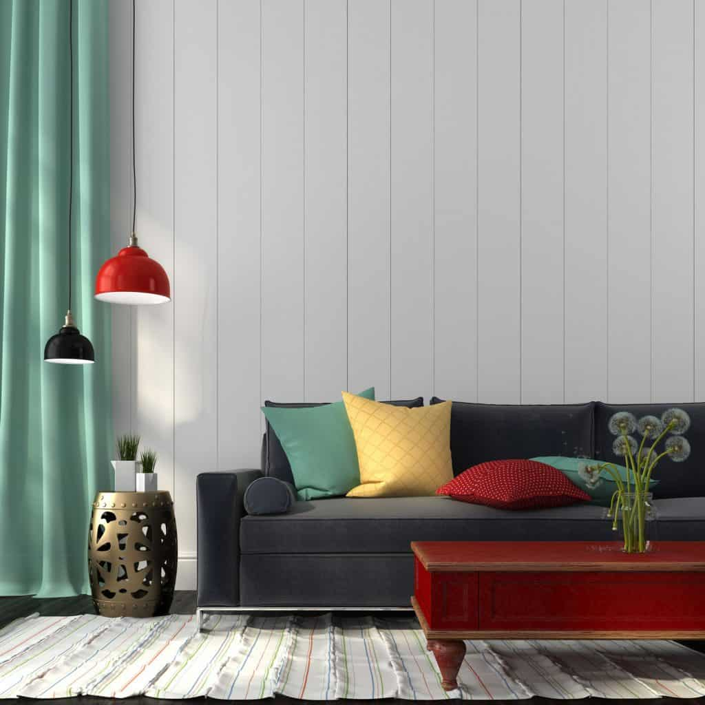A living room with a dark colored couch, a light green colored curtain, and bright colored pillows