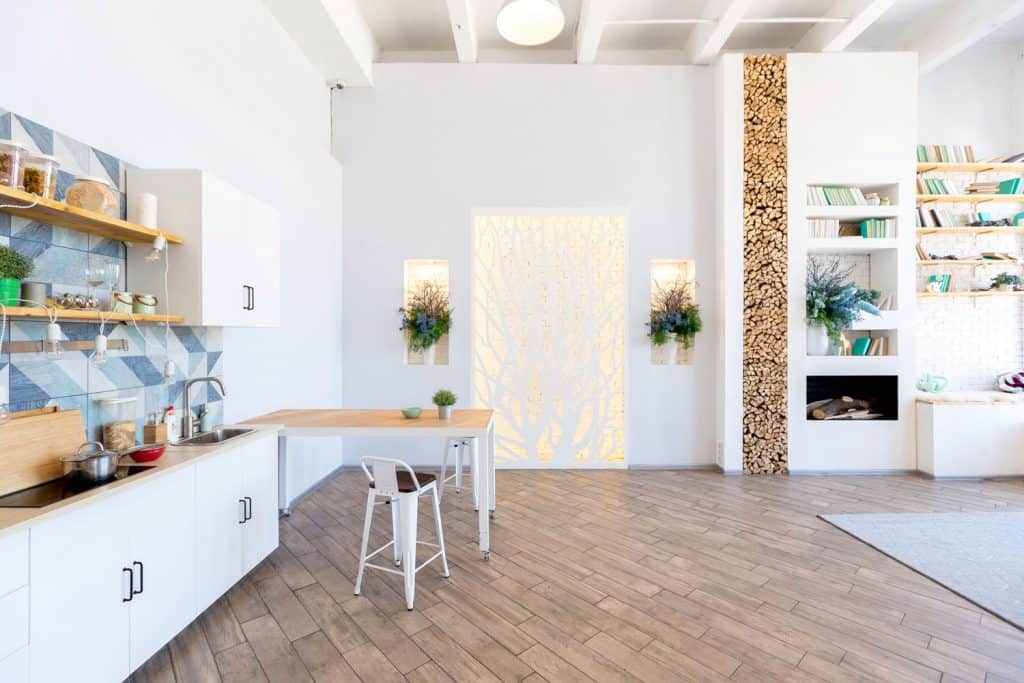 A luxurious and spacious conjoined kitchen and living room with laminated flooring and a blue and white backsplash on the kitchen section