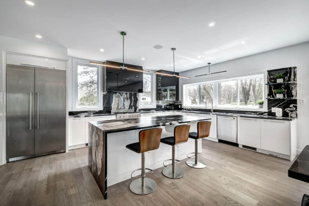 A luxurious modern kitchen with wooden laminated flooring, kitchen countertops made from marble and white paneled cabinets