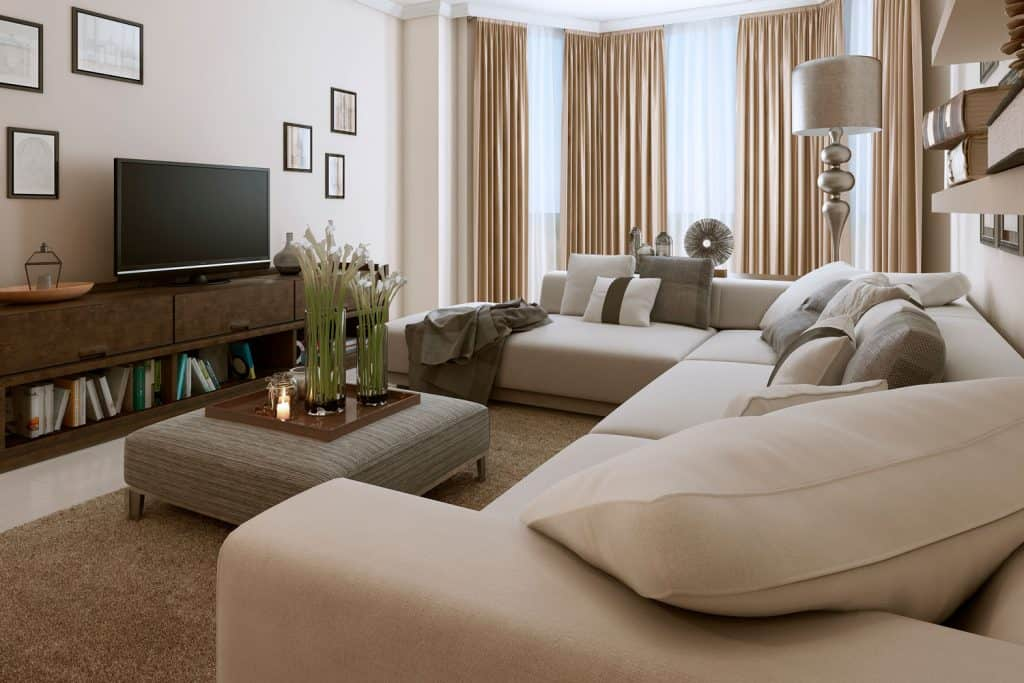 A luxurious modern living room with cream sectional sofa, gray ottoman and brown rug