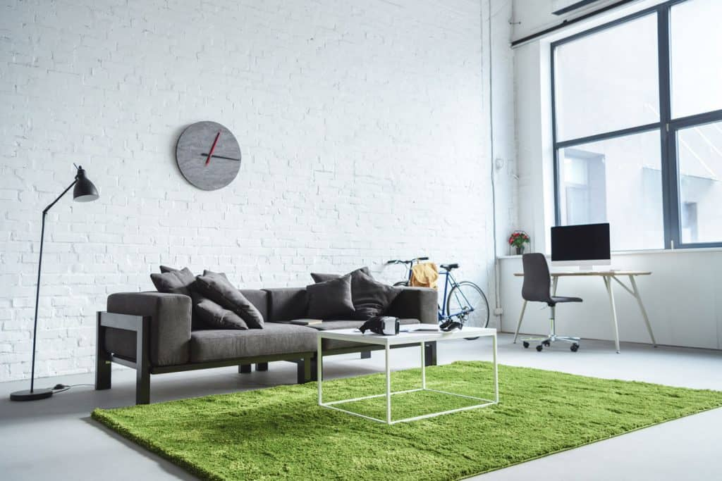 A luxurious working living room apartment with white painted brick patterned wall and a gray couch with green rug