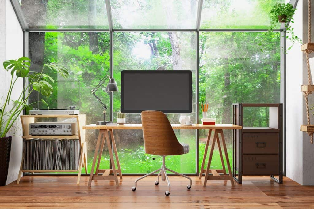 A luxurious working office area with a wooden working table and a computer with glass wall background making the backyard visible