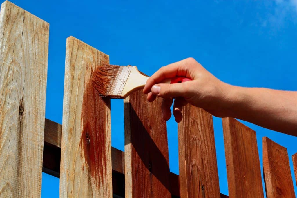 A man holding a brush and painting the fence with a brown color