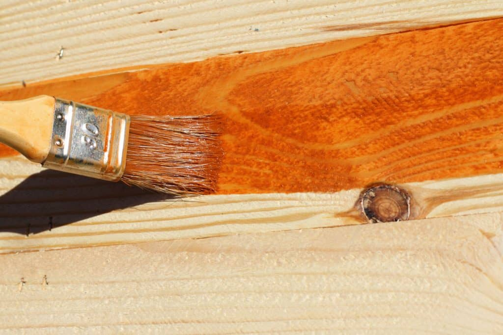 A man painting a wooden wall with varnish
