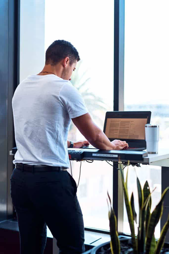 A man standing while working on his laptop