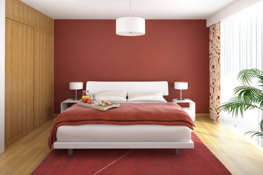 A modern bedroom with a red painted header wall and a huge window with a white curtain