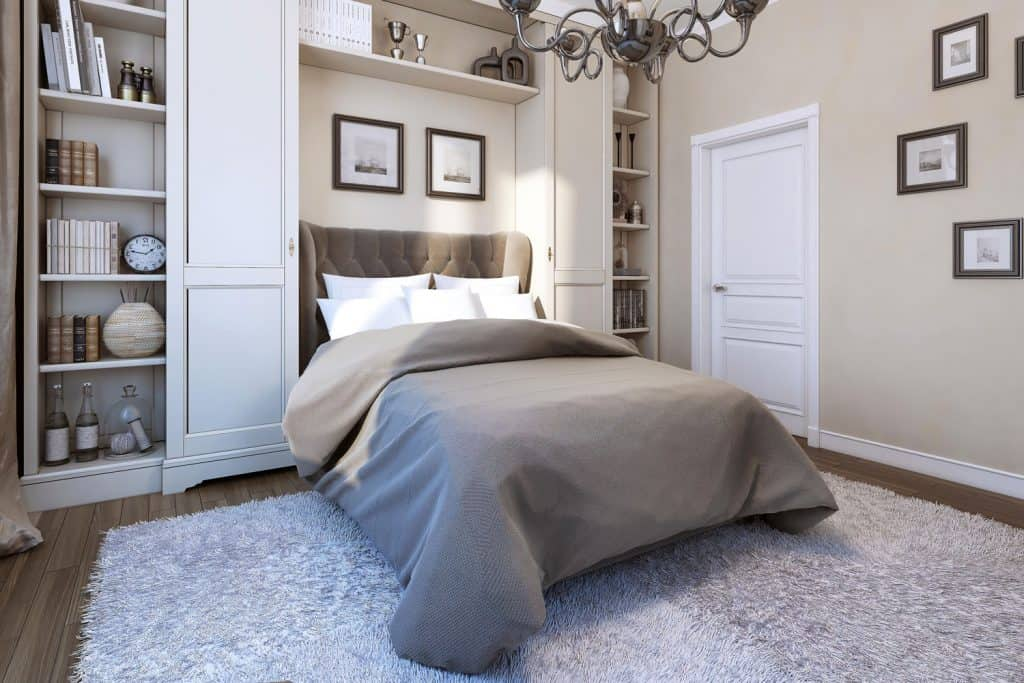 A modern bedroom with classic styled designs on the walls and a bed with gray beddings