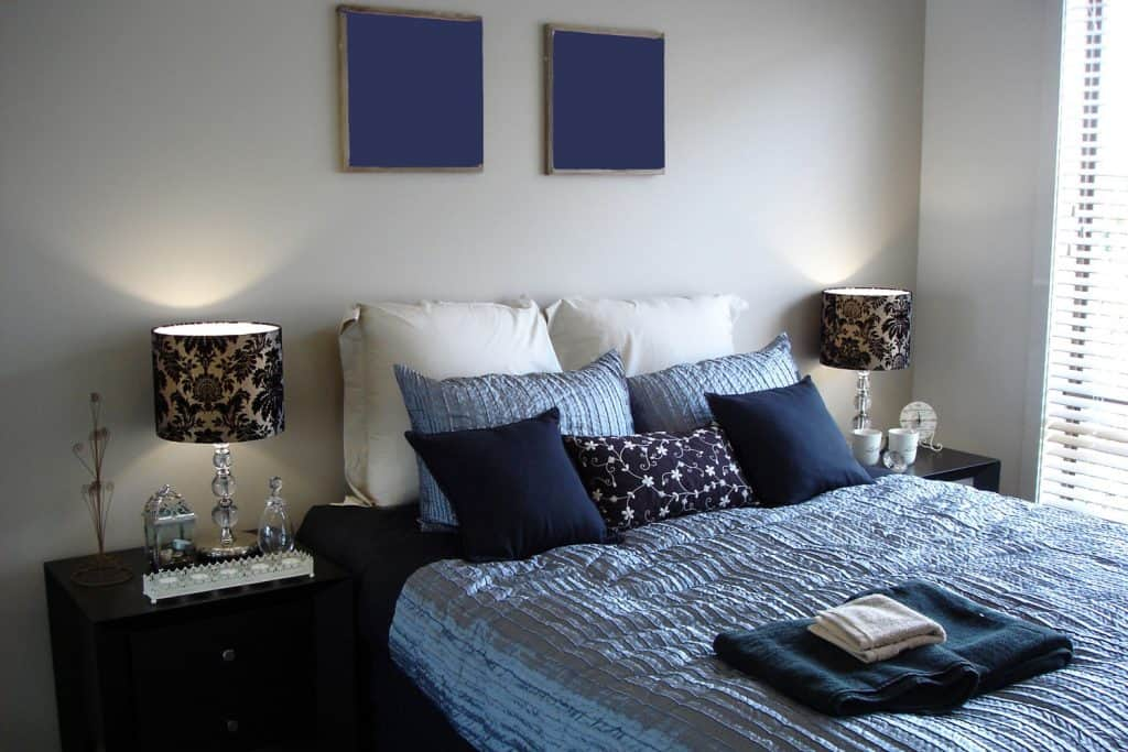 A modern contemporary bedroom with a classic styled beddings mixed with modern styled furniture