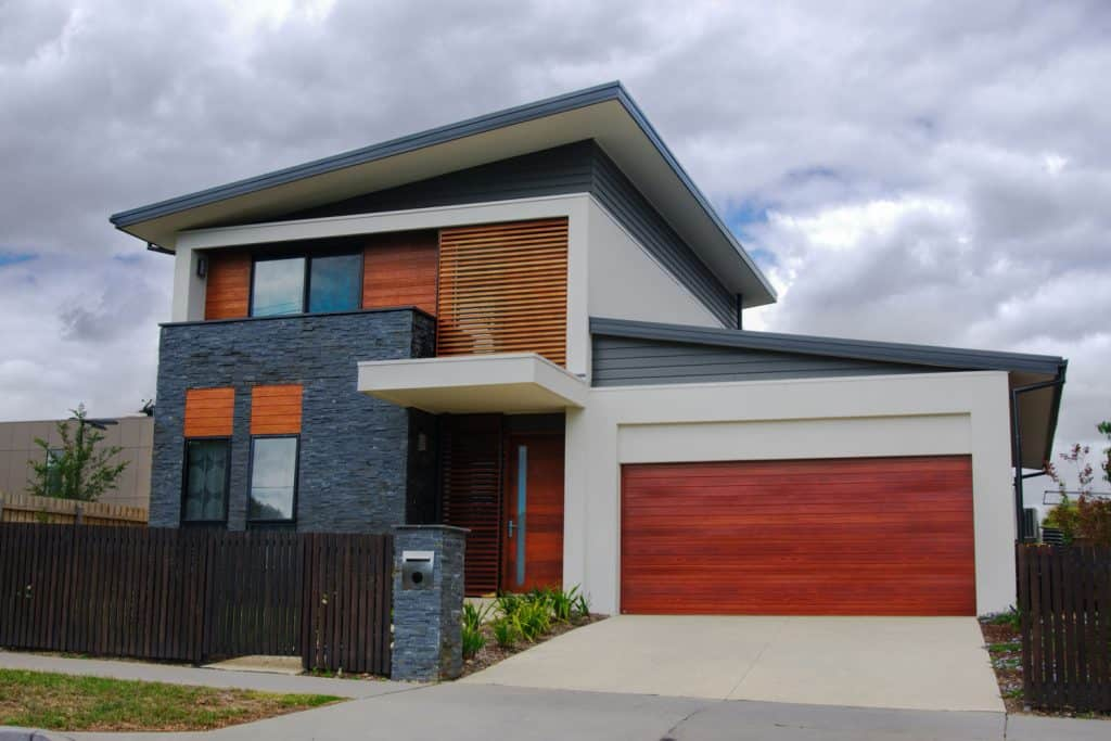 A modern contemporary house with brown dark painted fence and a beautiful modern fascade