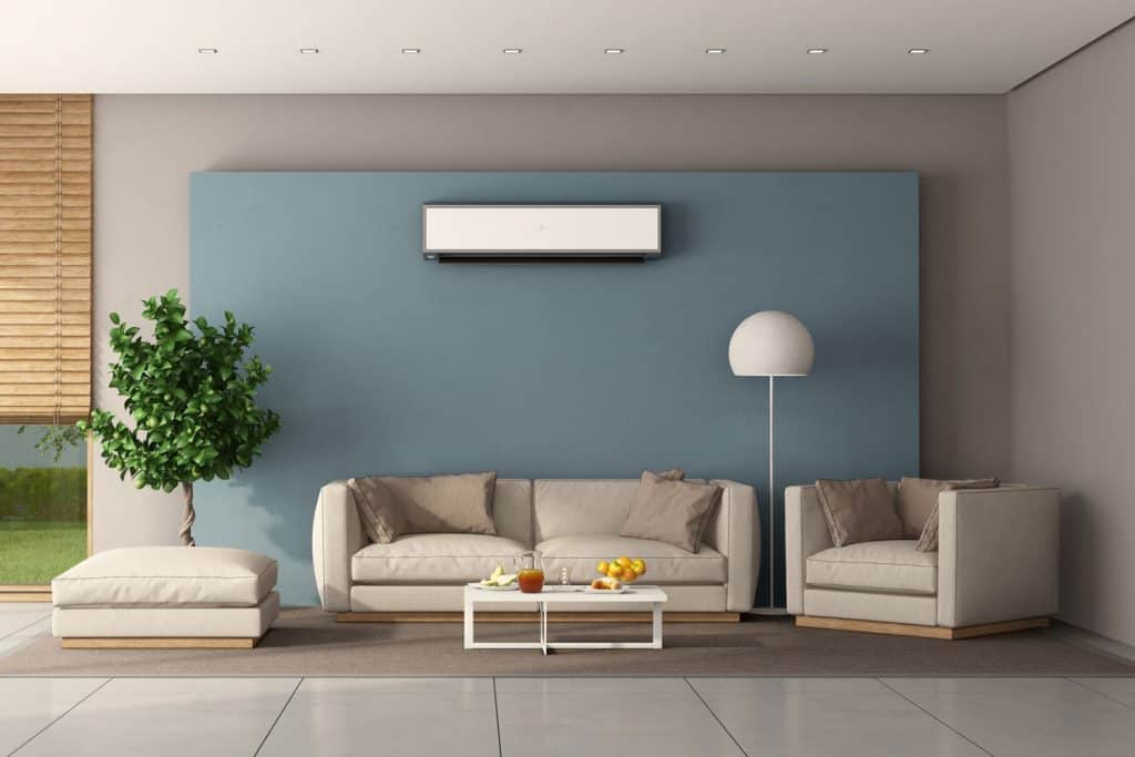 A modern contemporary living room with a blue accent wall with a split type air-conditioning unit on it