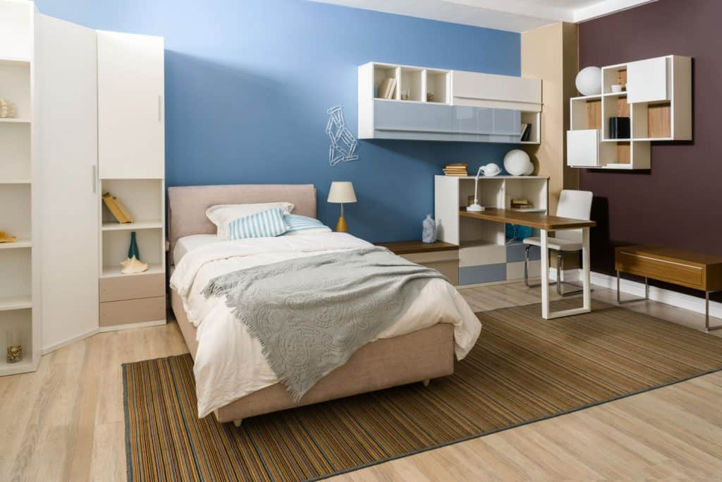 A modern contemporary bedroom with cabinets, tables, and a blue and brown accent wall
