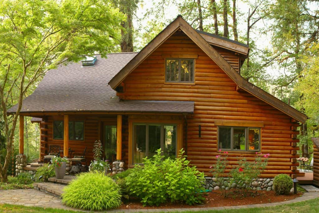 A modern forest log cabin with a beautiful front lawn and sliding windows