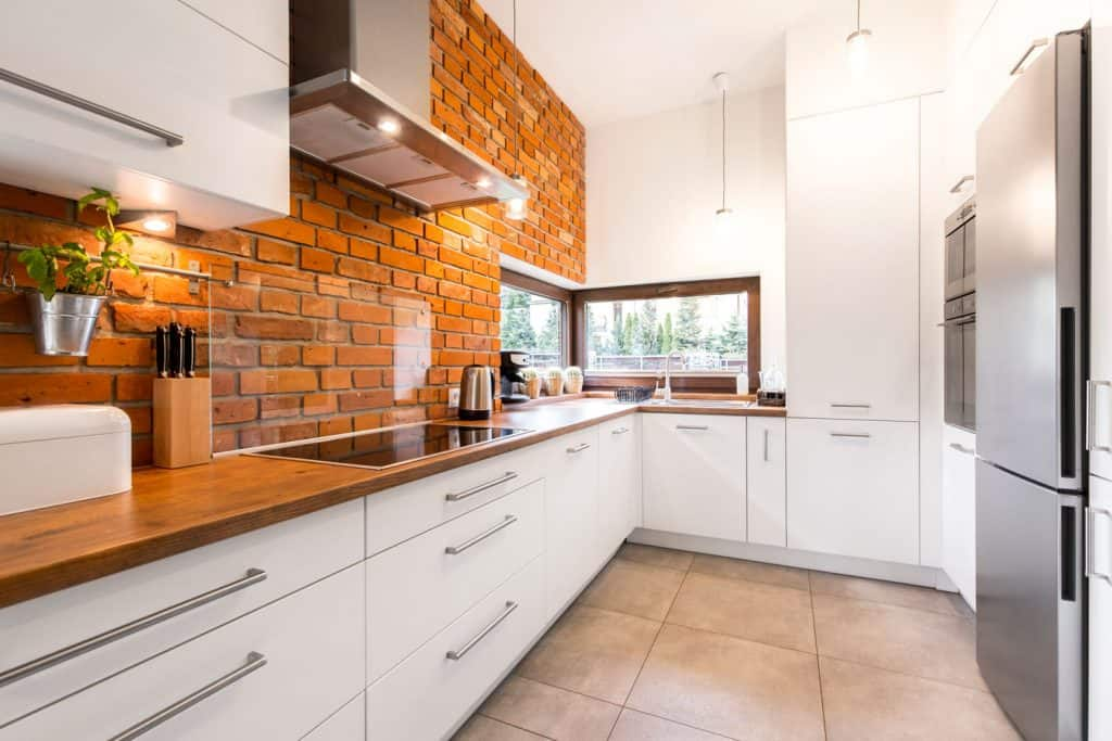 A modern kitchen with a brick backsplash incorporated with a wooden countertop