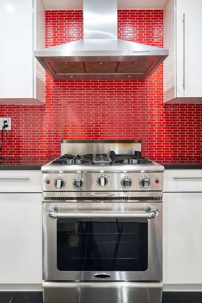 A modern kitchen with gorgeous red brick patterned backsplash