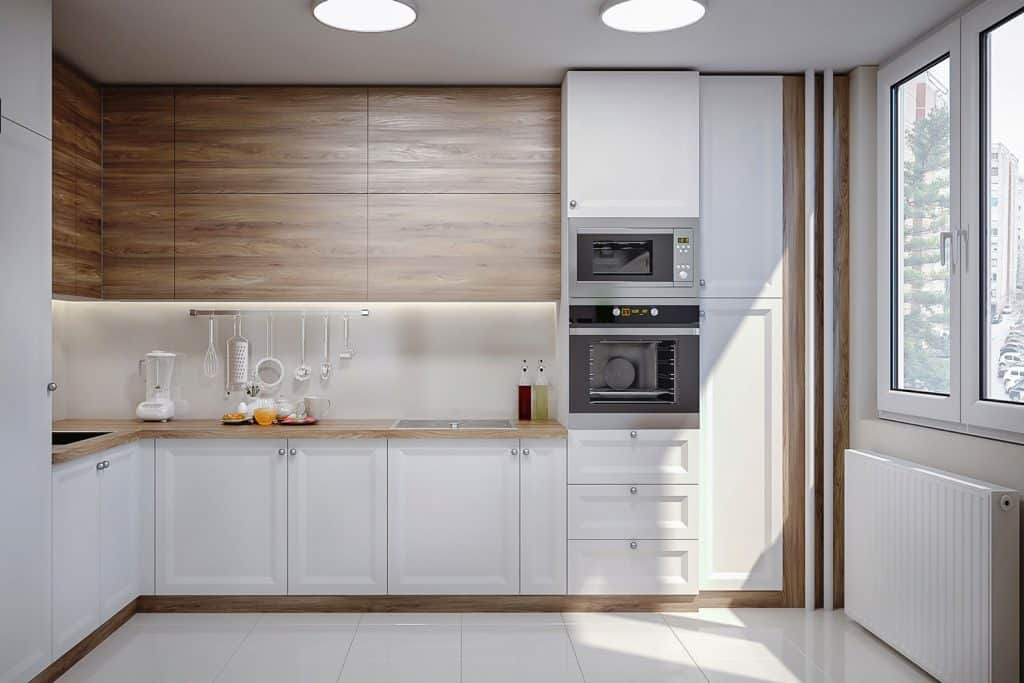 A modern kitchen with wooden paneling and white painted lower cabinet section