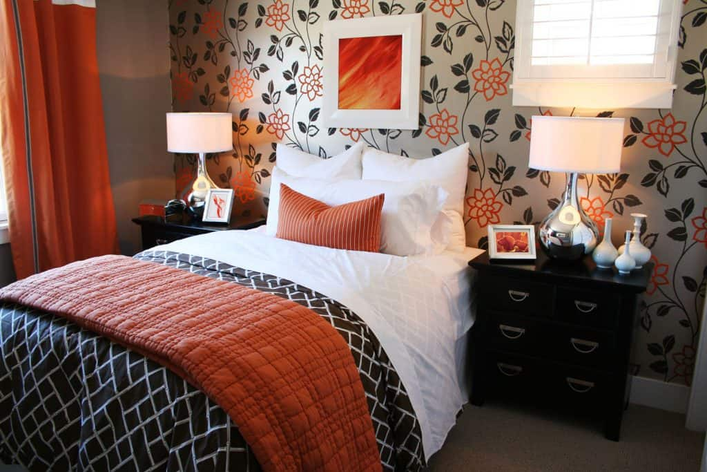 A modern three colored bedroom with a floral designed wall and a red curtain