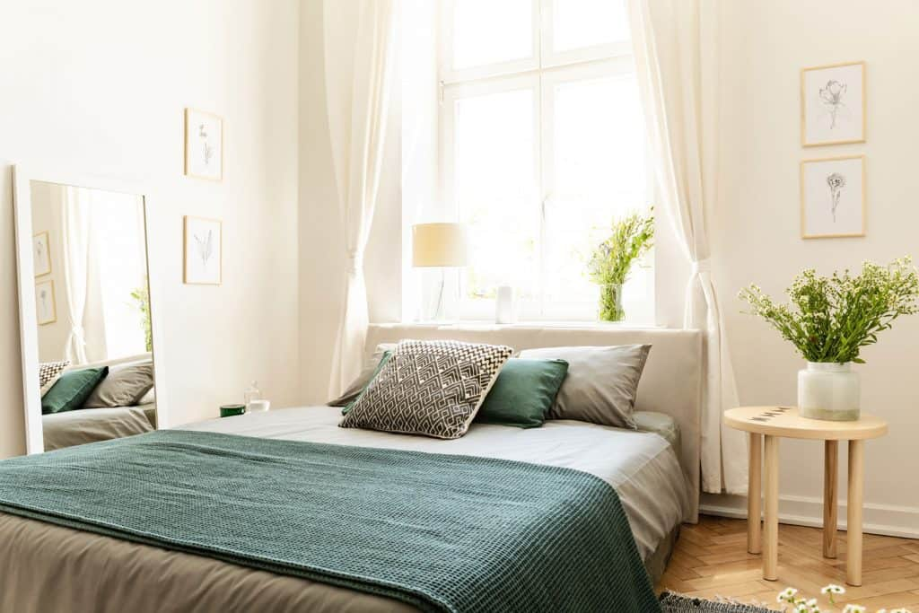 A modern well lit bedroom with a classic bed, white and teal colors, and indoor plants