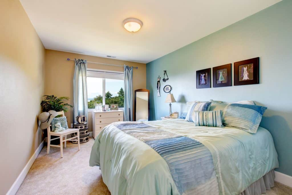 A narrow bedroom with a mixed blue and beige colored wall