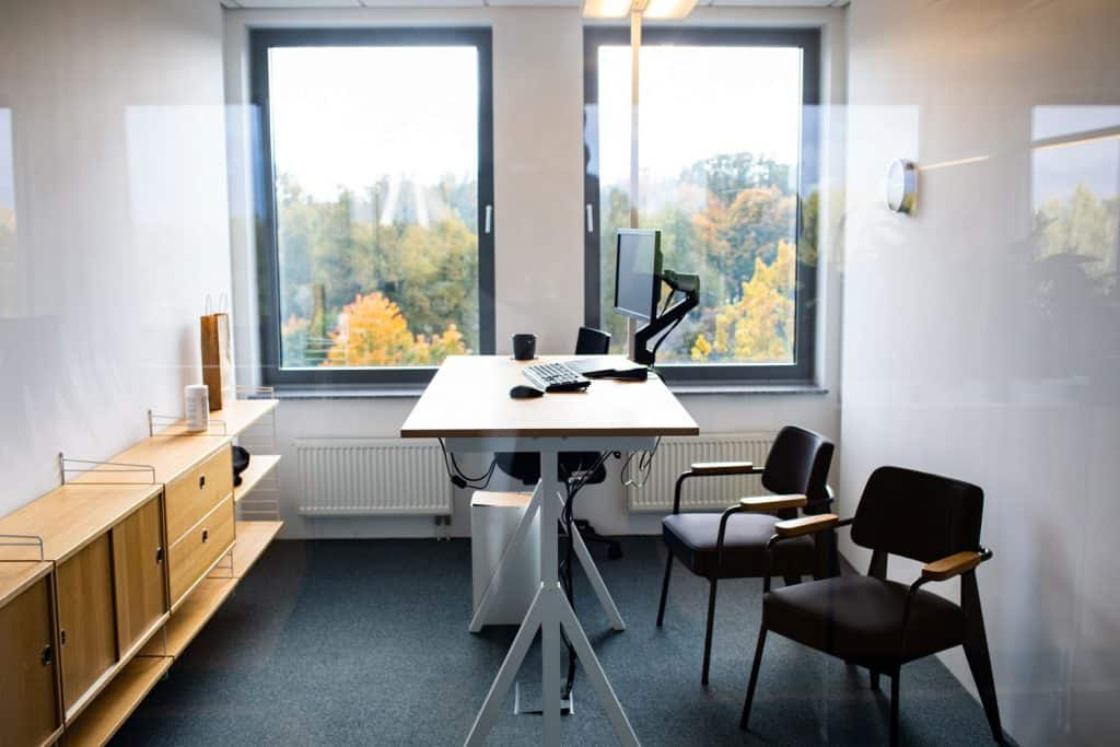 A narrow office area with a wooden table and a computer on the corner