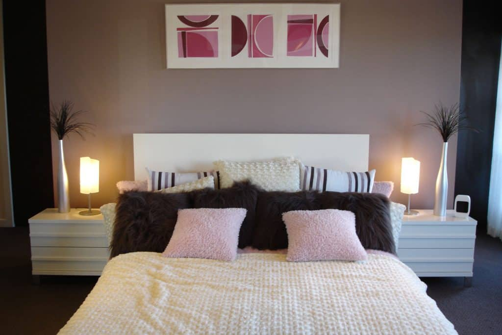 A purple and white themed bedroom with modern designs and a cozy bed