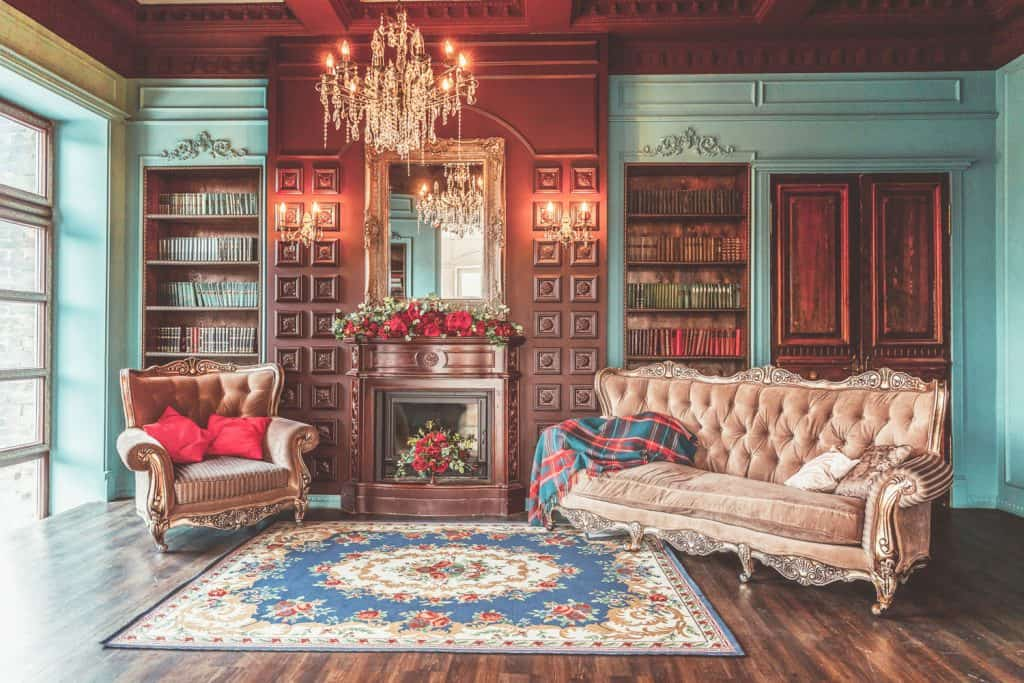 A reading area of a house with bookshelves books fireplace and old styled chairs