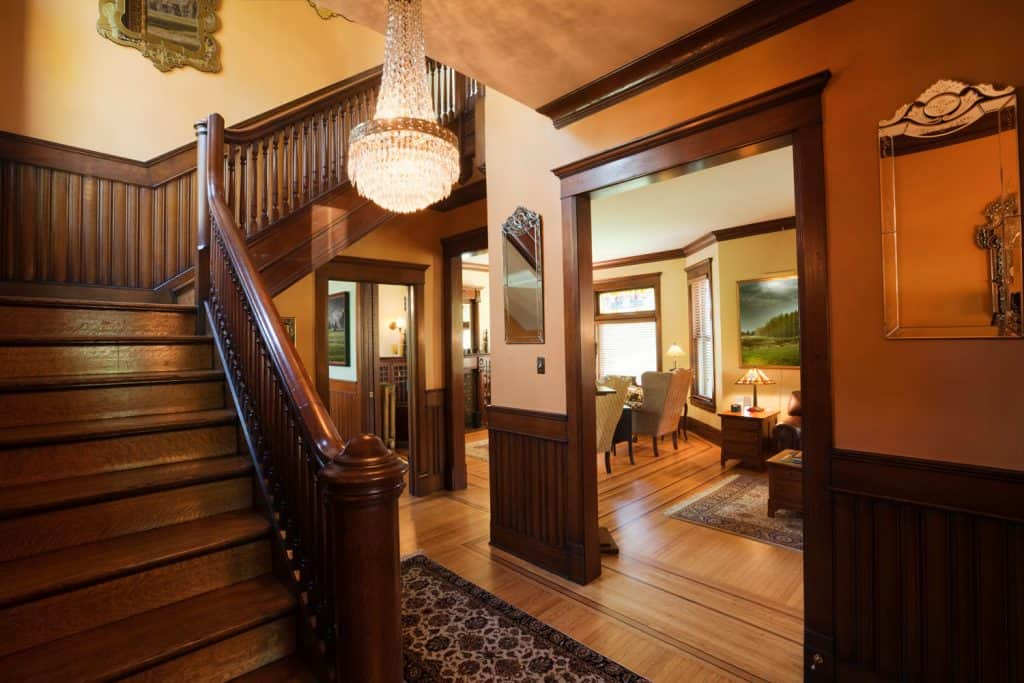 A rustic inspired foyer with wooden stairs and banisters, and hard wood flooring